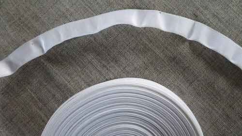 Curved white, easy-sew, petersham ribbon for low waistbands.