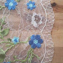 Scallop-edge tulle with embroidered flowers in blue and green